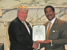 Former (MML) Maryland Municipal League President and Councilman Stewart Cumbo presenting Maryland House Speaker, Michael Busch, with a MML Certificate of Appreciation